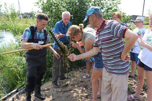 Ученые Денис Савосин и Андрей Хумала показывают ведлозерцам элодею канадскую